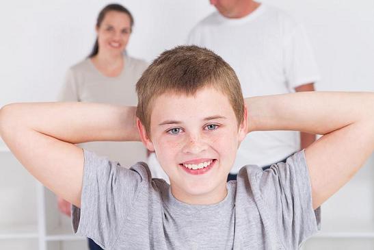 happy teen boy standing in front of parents